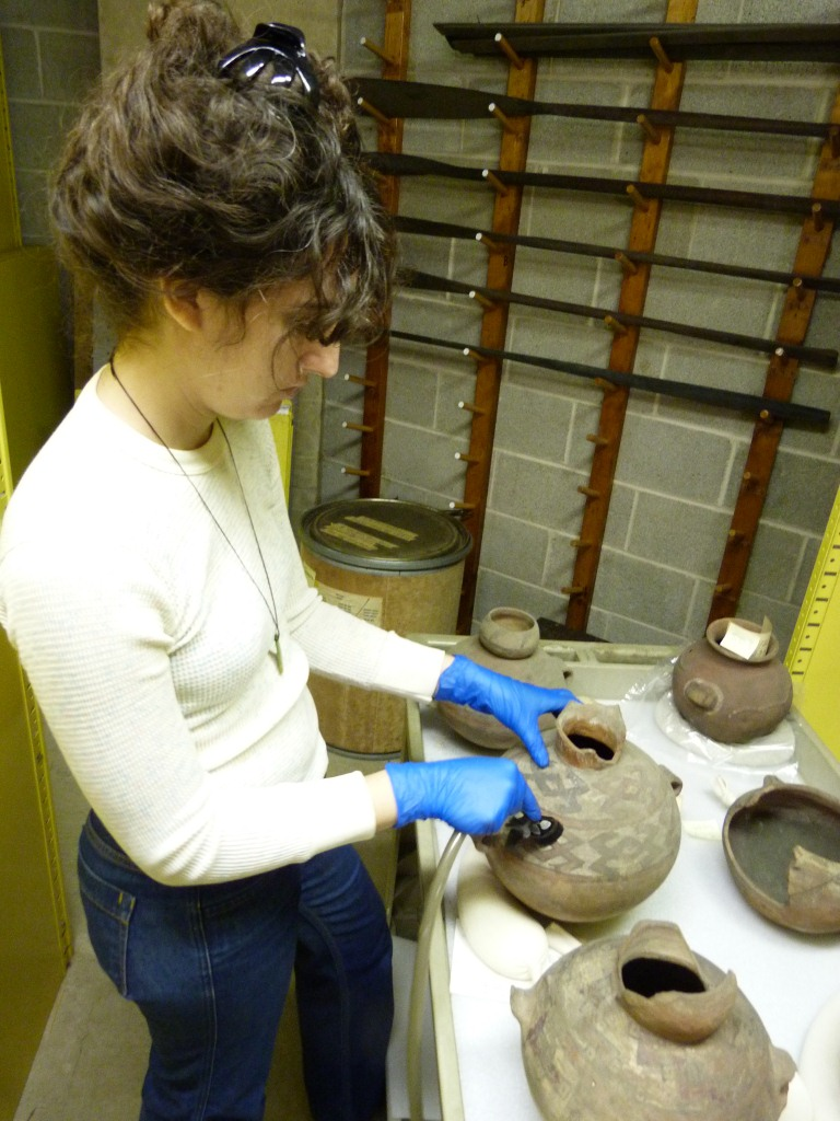 Elissa Meyers vacuuming ceramics