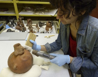 Pre-program conservation intern Elissa Meyers vacuums a pot