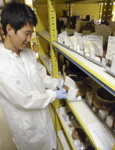 Pre-program conservation intern Hong Gyu Shin places a newly re-housed ceramic back on the shelf