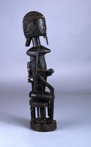 Wood and iron sculpture of a woman seated on stool with child