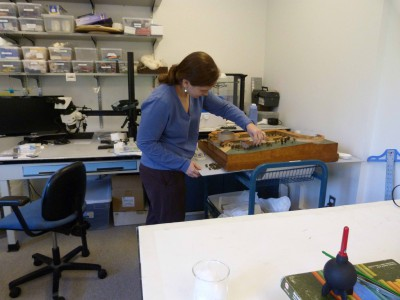 Pre-program intern Cassia Balogh works on a large architectural model in our current cramped lab space.  The model is resting on a rolling cart.