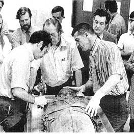 Photo from the 1972 autopsy. Dr. Michael Zimmerman (left) cuts into the mummy's wrappings with a Stryker saw, assisted by Dr. Aidan Cockburn (center) and Dr. Al Ryman (right).