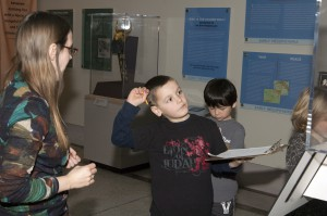 Inspired by an artifact on view, an Abington School District 2nd grader demonstrates the throwing of a spear in the Iraq's Ancient Past exhibition.  Photo: Dari Sutton