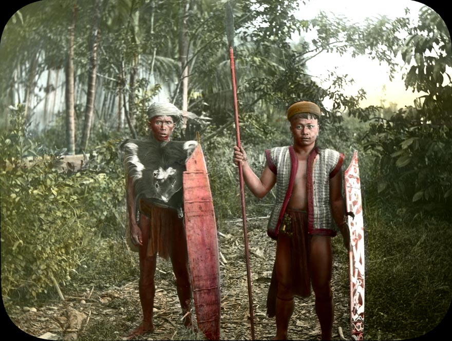 Tegang, a Dayak from Borneo was the guide of William Henry Furness III, Alfred C. Harrison, Jr., and Hiram M. Hiller on their trip to the interior of the island, 1896-1897.  Photograph by Alfred C. Harrison, Jr.; hand-colored by Katharine Gordon Breed.  Penn Museum image 216350