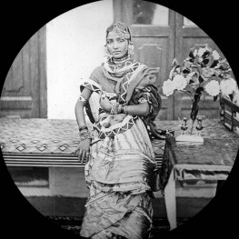 """""""Hindu Lady"""" leans against a table in a house with a bouquet of flowers by her side. This is one of the many glass lantern slides in the Penn Museum archives collection. (Museum Image No. 215377)"""