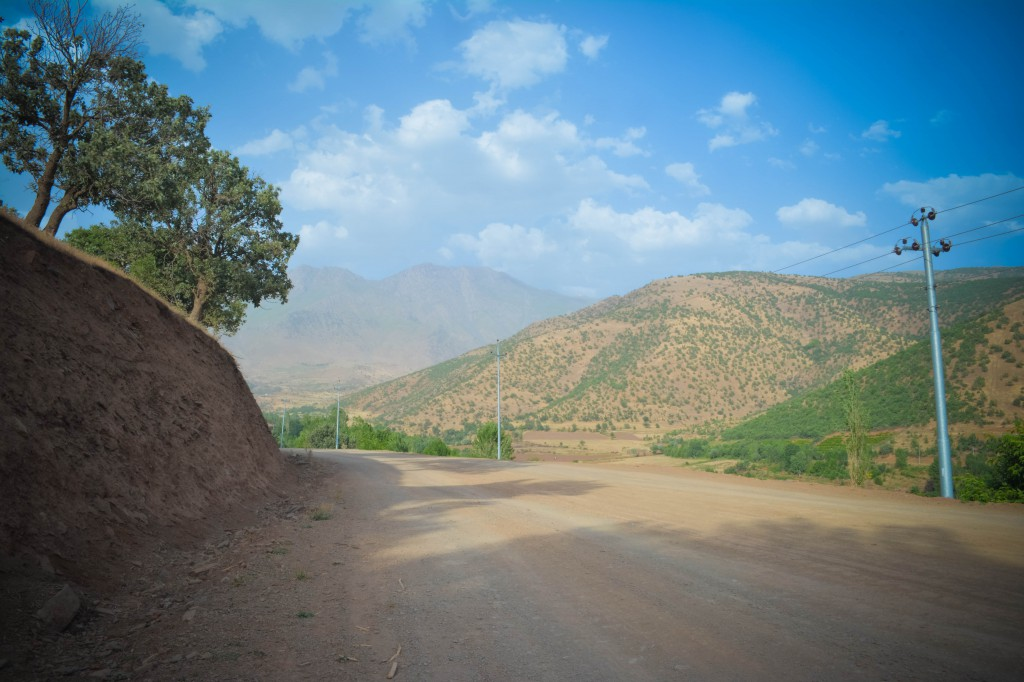 Survey along the road-cut (left) with the highest peaks of the Zagros in the background
