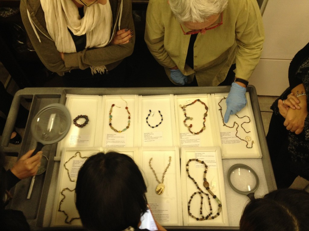 Dr. Jane Hickman shows students jewelry from the Museum's collections.