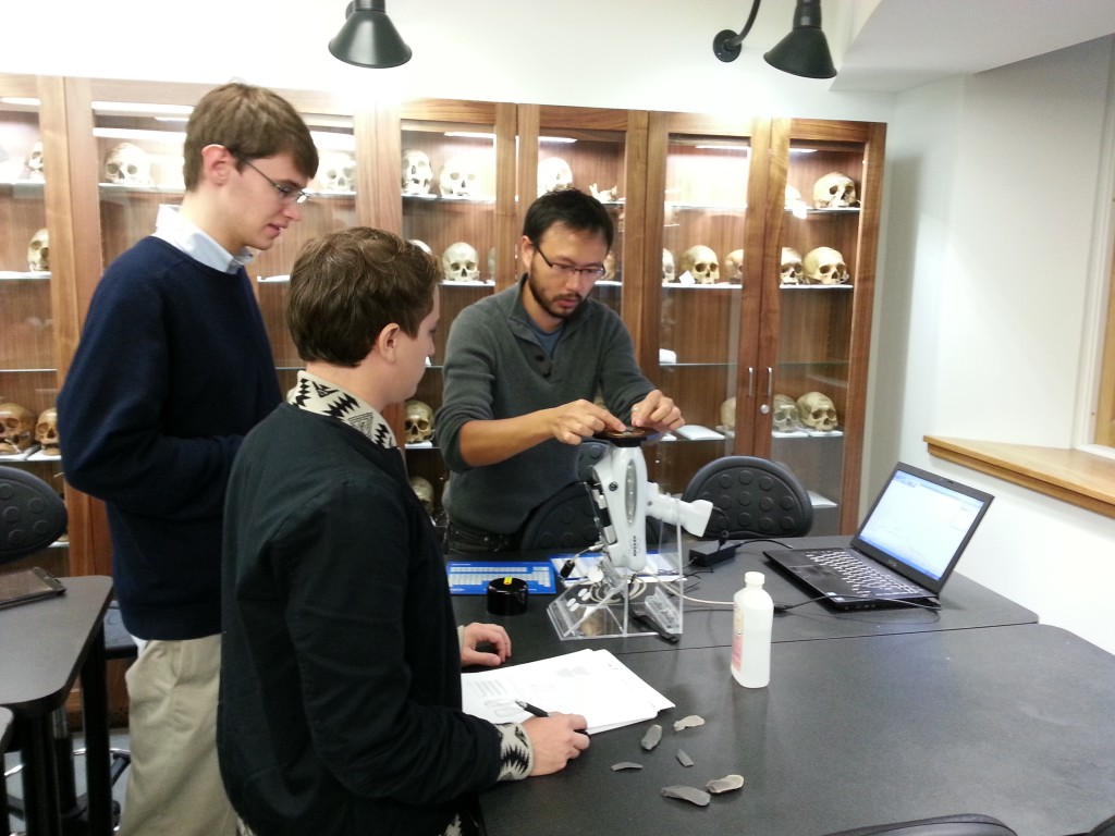 Lithics expert Sam Lin demonstrates using a portable X-Ray florescence unit to students.