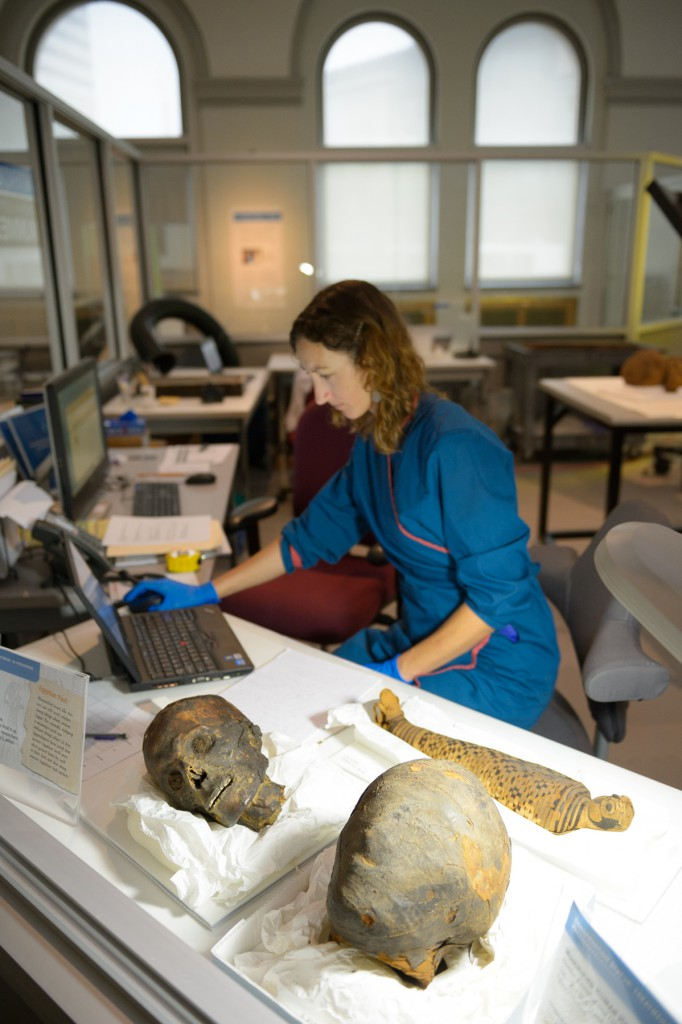 "Project Conservator Molly Gleeson at work in the ""In the artifact Lab"" exhibition. Photo by Jim Graham."