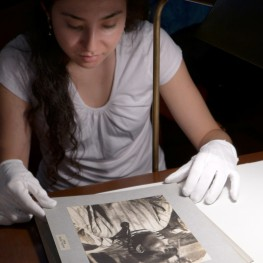 Enika Selby in the Penn Museum Archives, examining photos of Inuit women in fur garments. Photo by Margaret Bruchac.