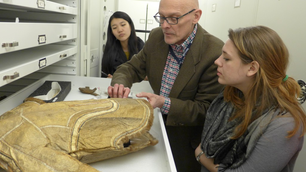 William Wierzbowski examines an Alaskan gutskin coat in the Arctic collections, with students Elizabeth Peng and Alexandria Mitchem.  number 39-10-1. Photo by Margaret Bruchac.