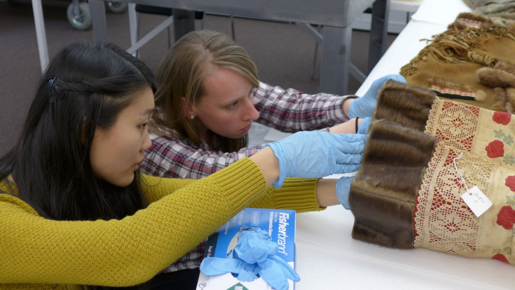 Elizabeth Peng and Karen Thomson, in the Penn Museum Study Lab, examining a pair of Inuit women's boots with Victorian lace traim. Photo by Margaret Bruchac.