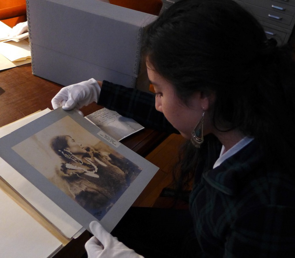 Figure 4: Enika Selby in the Penn Museum Archives, examining photos of Inuit women in fur garments. Photo by Margaret Bruchac