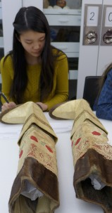 Elizabeth Peng examines Eskimo (Inuit) women's boots from Greenland, in the Penn Museum Collections Study Lab. Photo by Margaret Bruchac, with permission of the Penn Museum.