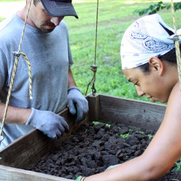 Zhenia and our intrepid volunteer, Tim, sift dirt through a 1/2-inch screen.