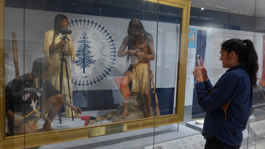 A very meta image taken by a Native faculty member, of her Native graduate student using her iPhone 6 camera to photograph historic Native mannequins holding cameras and iPods in an exhibit case. In the Royal Ontario Museum. Photo by Dr. Bruchac.