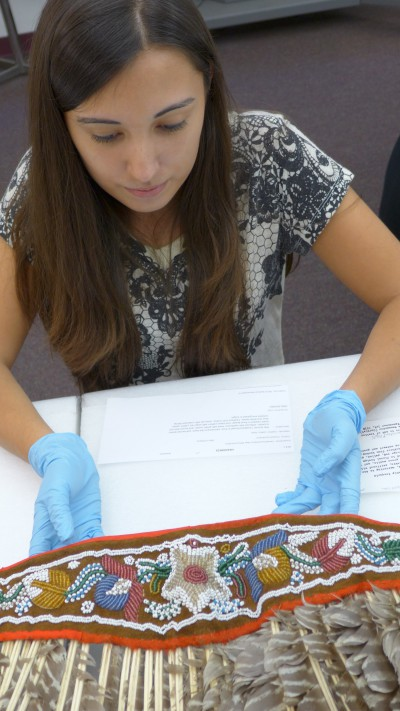 Danielle Tiger examines an eastern turkey feather headdress at the Penn Museum.