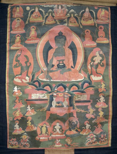 Thangka painting of Bhaisajyaguru, the Medicine Buddha, with his associated deities of Suryaprabha, Chandraprabha and the 7 Buddhas of Medicine. Thangkas are paintings which are often used as meditational aids. The Buddha holds a bowl made of lapis lazuli which holds a divine healing nectar (amṛta) which is meant to be received through meditation. (51-41-9)