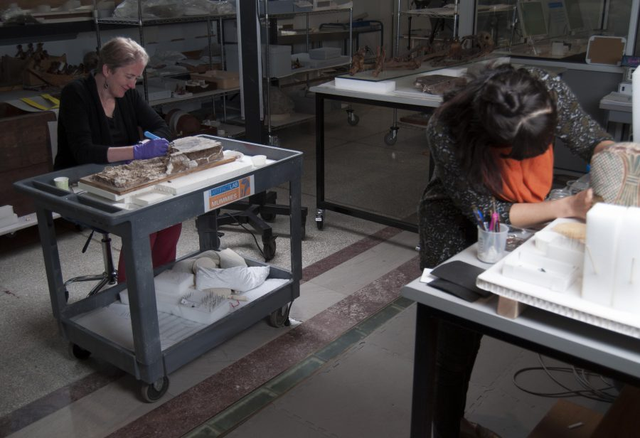 Emily happily working away on a wall painting fragment, with conservator Alexis North in the foreground