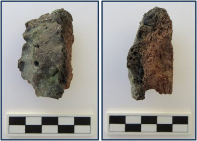 A front (left) and side (right) view of a possible crucible fragment with copper slag melted onto it. The slag-covered crucible was found during the 2004 excavations of Dr. Vanessa Smith. A centimeter scale is included at the bottom of each picture. Photo by Paul Verhelst.