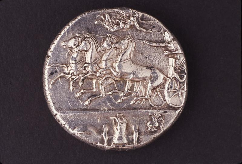 Silver dekadrachm of Syracuse, by the artist Euainetos, early 4th century, features Nike flying about to crown a charioteer.