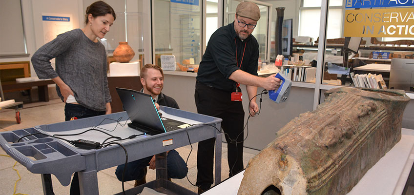 Museum employees scanning object