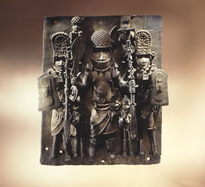 A high-ranking military chief dominates this 16th century plaque, one of nearly a thousand that decorated Benin palace courtyards. Accompanied by an entourage of lieutenants, musicians and pages prepared to fan him, the chief dances at the palace war festival.