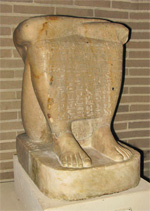 "This statue depicts the priest Horwedjau.  The inscription, which covers the front of the statue calls upon the priests of the Temple at Coptos to make invocation offerings at various festivals for the benefit of his ka (or ""life force"").  The god Min was the primary deity of Coptos and his name appears in the first line of the inscription. The inscription also includes a funerary offering prayer invoking Isis of Coptos.  The head of the statue is missing and the feet and front of the base are restored.  This shape of statue is known as a block statue, a form which first appeared in the Middle Kingdom (c. 1980-1630 BCE) but remained popular centuries later."
