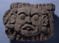 Sun God, Copan, Honduras, limestone, Late Classic Period, 750 A.D. This head of an important celestial deity has jaguar ears, scroll eyebrows, fish fins on his cheeks, and a single filed tooth. This god is often identified with Venus and the sun. Originally, this may have been a shield held by one of the figures on the Hieroglyphic Stairway in Copan, or perhaps a decoration for the building at the top. Penn Museum Object 153008.