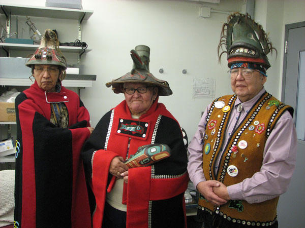 During a Tlingit consultation visit in January 2008, Andrew Gamble, Jr. (Kaagwaantaan clan leader), Herman Davis (L'ooknax. ádi clan leader), and Tom Young (Kaagwaantaan Box House leader) donned Tlingit clan regalia, including three hats in the Penn Museum's collections. Photo by Robert W. Preucel.