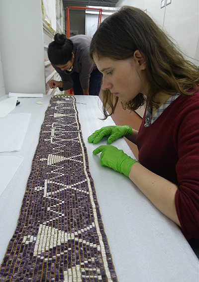 "Stephanie Mach and Lisa Puyo, Penn graduate students in anthropology, examining the Kanehsatake ""Two Dog Wampum"" belt in May 2014, at the McCord Museum in Montreal, Quebec. Photographs by Margaret Bruchac."