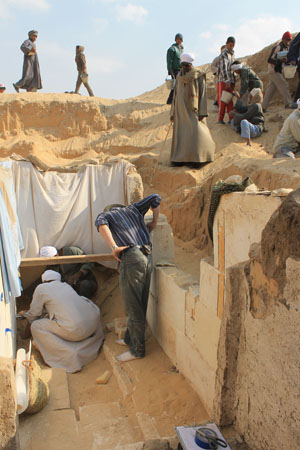 Team members work to excavate the burial chamber of the pharaoh Woseribre Senebkay, with sheets covering a painted wall decoration. Photo: Josef Wegner, Penn Museum.