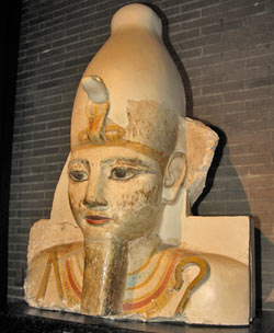 Head of a Colossal Statue of Ramses II, Abydos, Dynasty 19, Reign of Ramses II (1290-1224 BCE), Limestone (restored), Penn Museum Object 69-29-1. Depicted here is the bust one of a series of colossal figures that originally decorated the front of a row of rectangular pillars in the courtyard of a small temple at Abydos.  The king is depicted mummiform in the style of the god Osiris.  The king holds the symbols of kingship, the crook and flail, in his now missing hands.  Since the figure was intended to tower over any human below, the eyes look down.  Much of the original color remains.