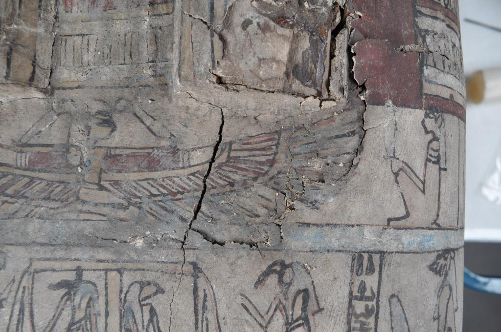 A detail of a badly damaged area on the coffin, showing significant cracking and flaking and detached and displaced fragments