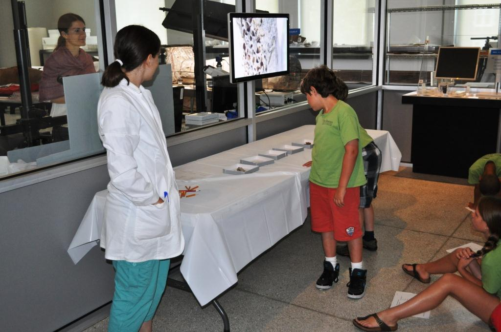 "A camper compares reference materials to the magnified image of the ""mystery"" material on the monitor"