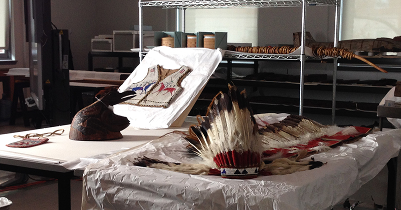 A variety of Native American objects currently in the Artifact Lab, including a war bonnet, baskets, a harpoon, a beaded vest and a wooden helmet.
