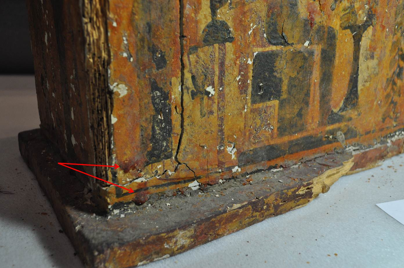 A detail of the shabti box showing areas where the coating is particularly thick (pointed out here with the red arrows).