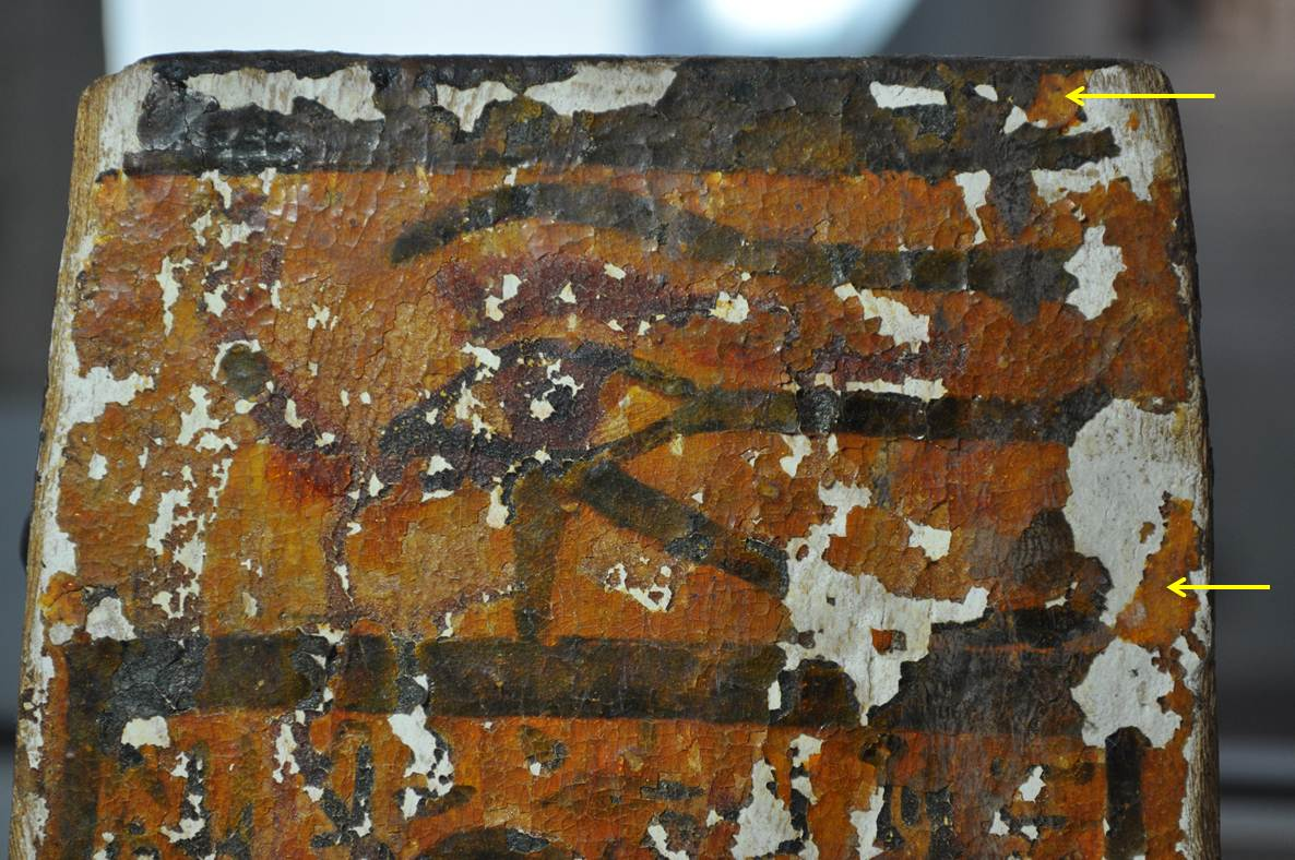A detail shot of one side of the shabti box - the yellow arrows are indicating areas where the coating extends over an area of paint loss onto the gesso.