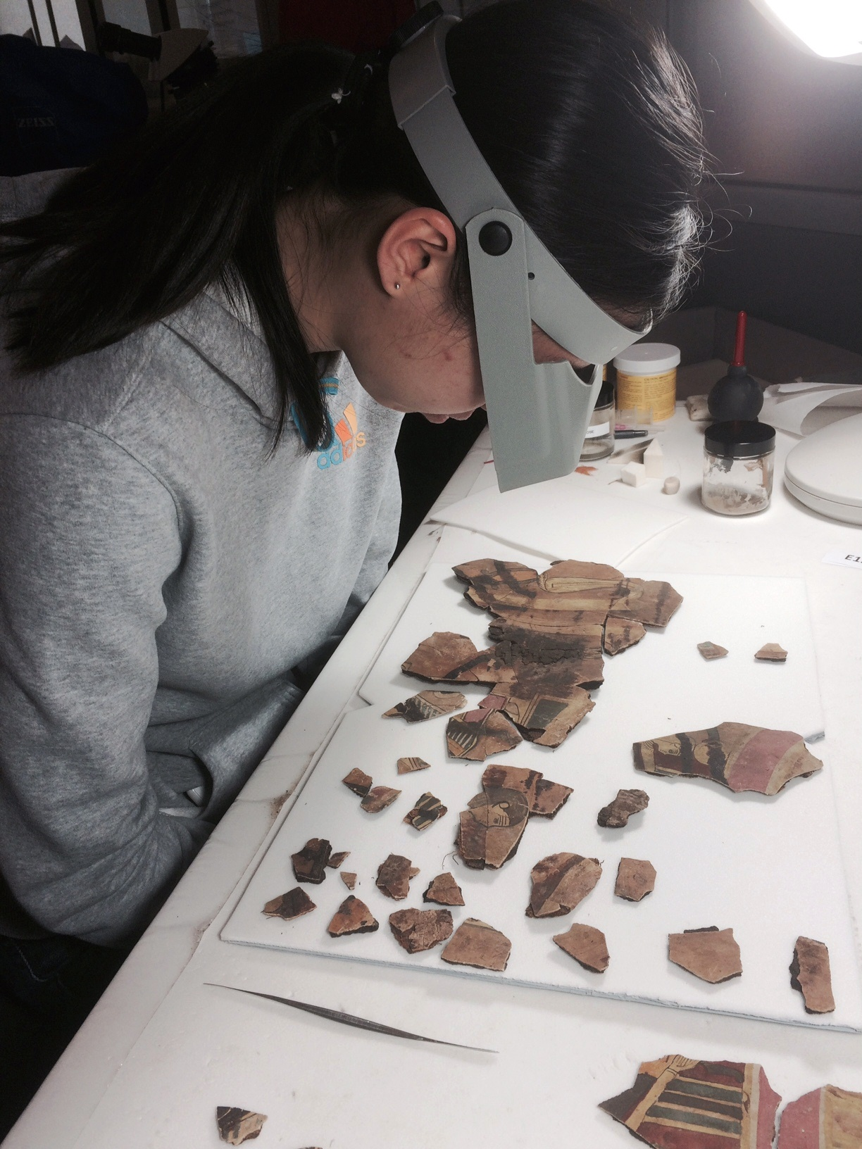 Pre-program intern Yan Ling examines the cartonnage fragments with the aid of an optivisor.