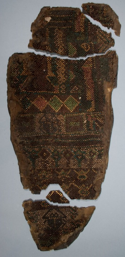 Sections of a beaded mummy shroud covered in wax