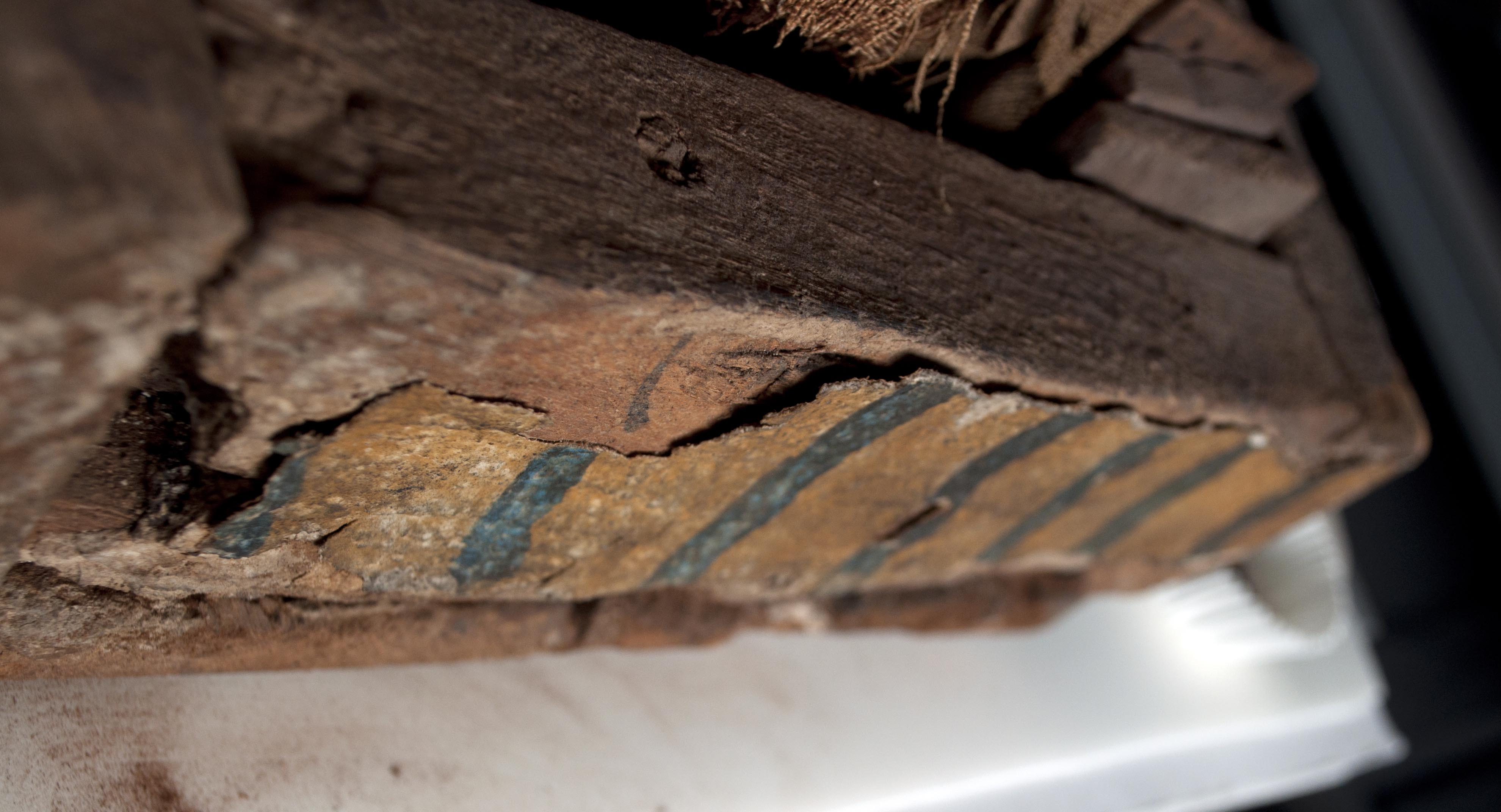 Detail of the exterior foot of the coffin, showing separation of the linen, plaster, and paint from the wood.