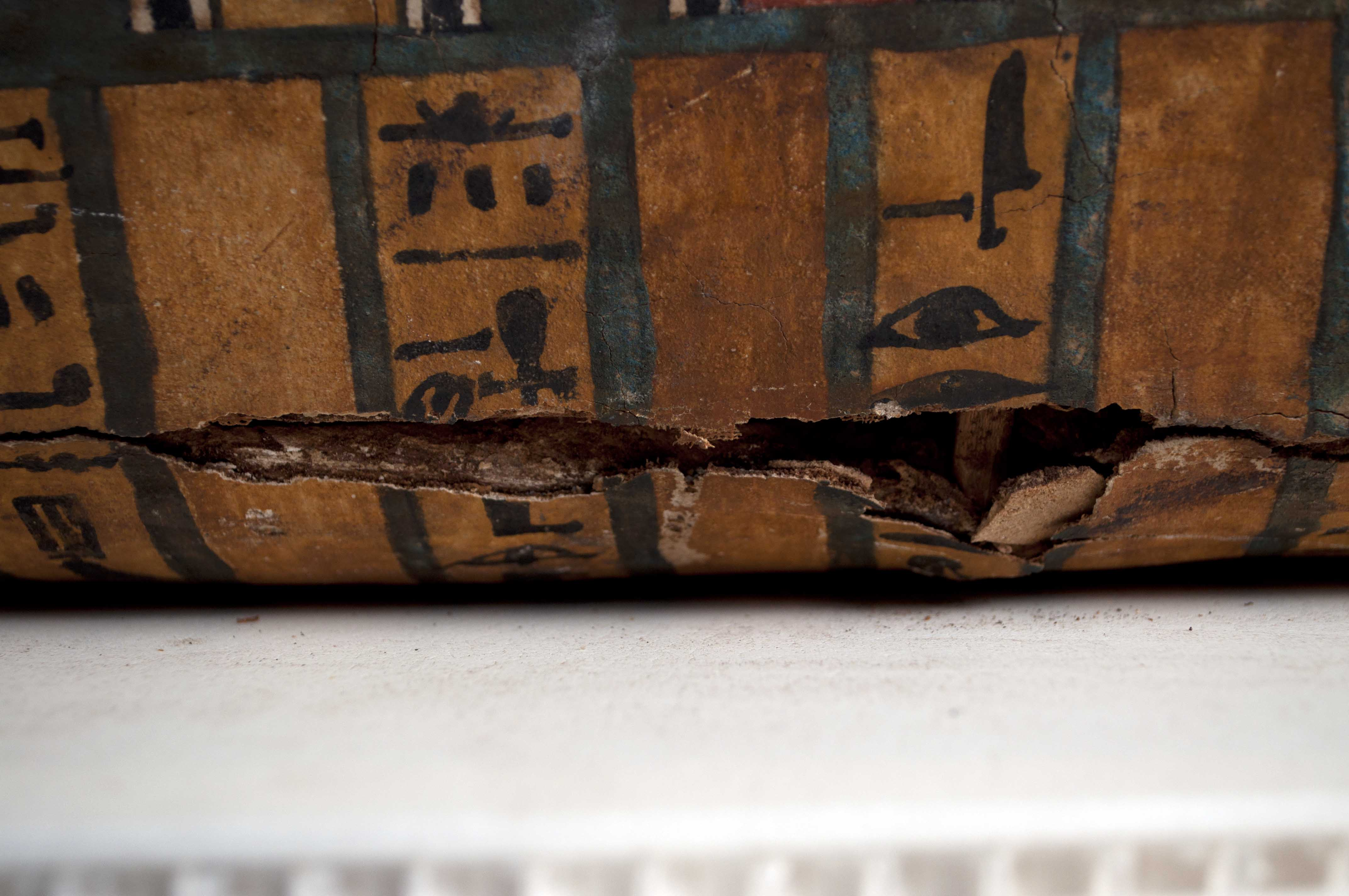 Detail of damage on the proper left side of the coffin.