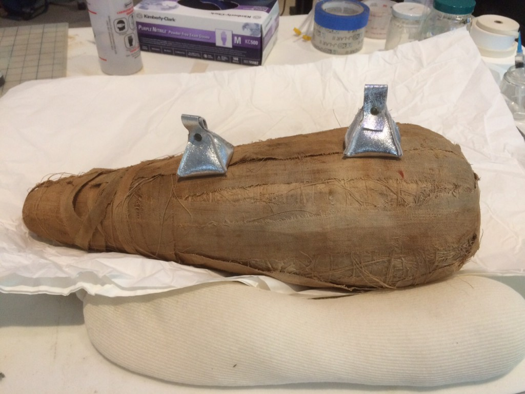 "A view of an ibis mummy during treatment to stabilize loose linen wrappings (the silver ""kisses"" are small weights)"