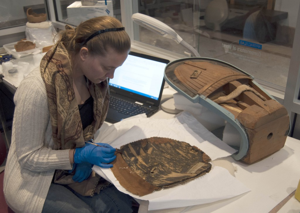 Eve examining the backside of the cartonnage, recently freed from the old mount, seen on the right side of this photo.