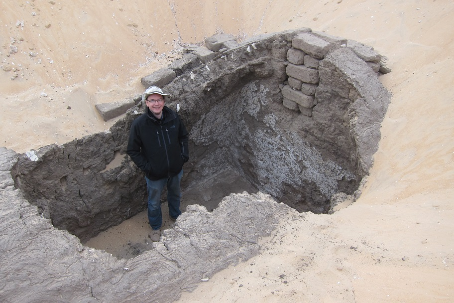 Dr. Kevin Cahail standing inside a recently-excavated building