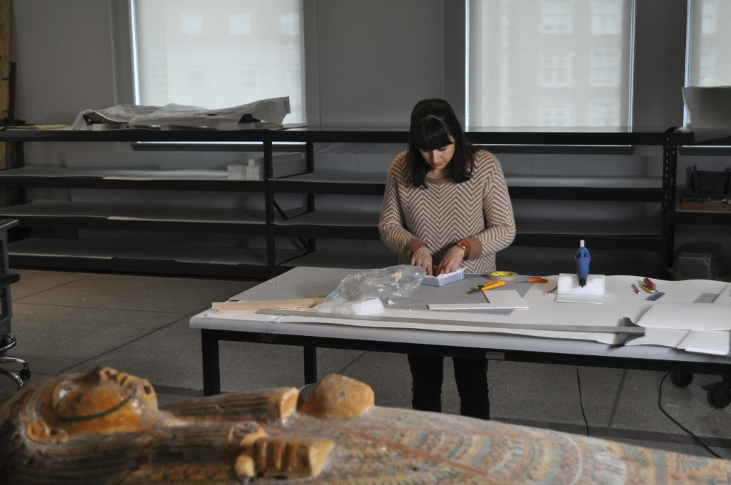 Conservator Alexis North working in the Artifact Lab with emptied shelves in the background
