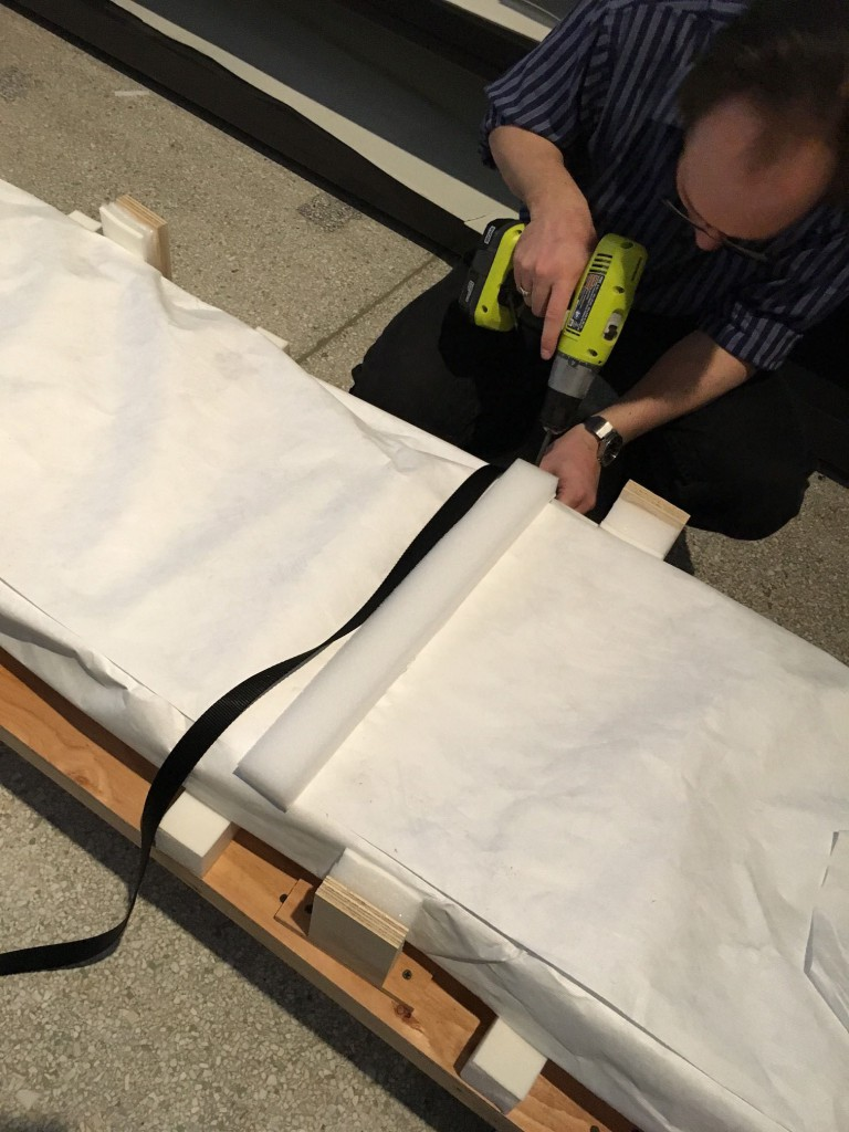 Kevin Cahail secures one of the coffin boards to its custom-made palette in preparation for moving off-site