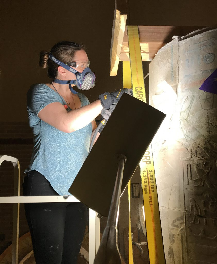 Project Conservator Anna O'Neill Alexander uses a PaleoTool to remove old restoration plaster that surrounds an ancient Egyptian limestone fragment.  The limestone fragment is part of a column from the palace complex of Merenptah,  which dates to 1224-1204 BCE.