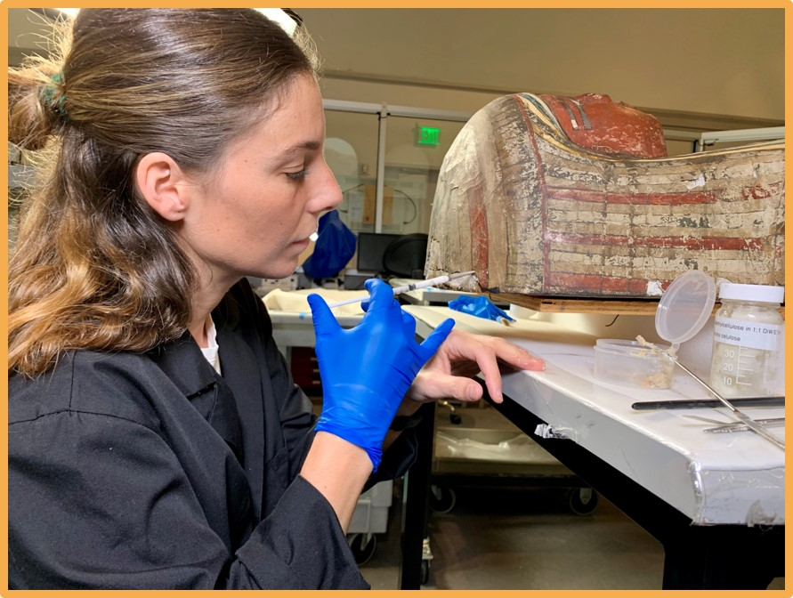 Project Conservator Teresa Jimenez-Millas is currently working on the coffin  and mummy of Petiese in the Artifact Lab. Here she is using an adhesive  solution to stabilize the painted surface of Petiese's coffin lid.
