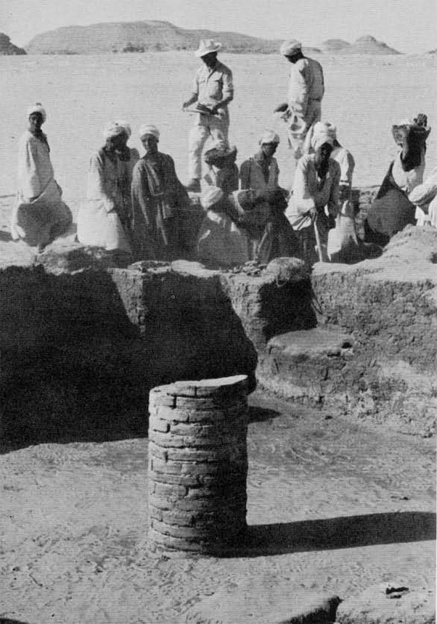 Photo of men around baked bricks.